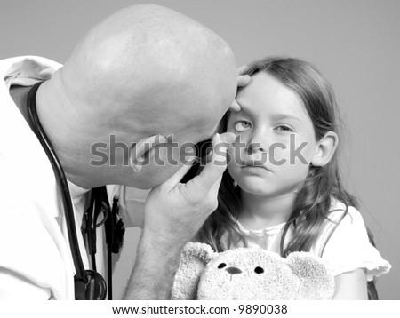 Physician Examining Girl's Eye - stock photo