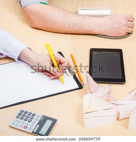 physician makes appointment and measures blood pressure of patient - stock photo