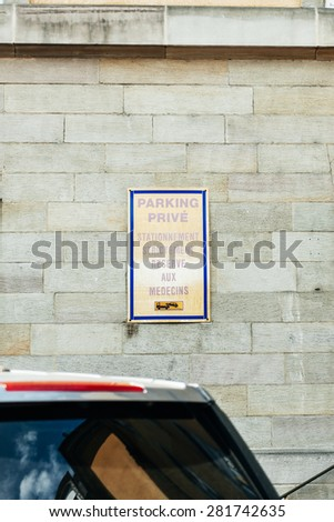 Physician parking space sign just in front of hospital with parked nearby cars - stock photo
