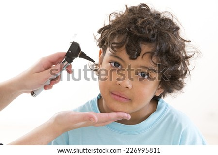 Physician performing ear examination during a visit - stock photo