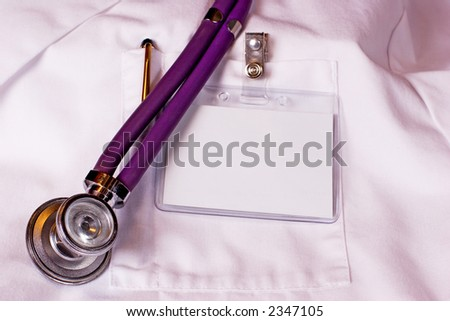 Physician's white labcoat with blank name badge, pen, and stethoscope. - stock photo