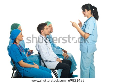 Physician woman giving explanations to her colleagues doctors sitting on chairs at seminar - stock photo