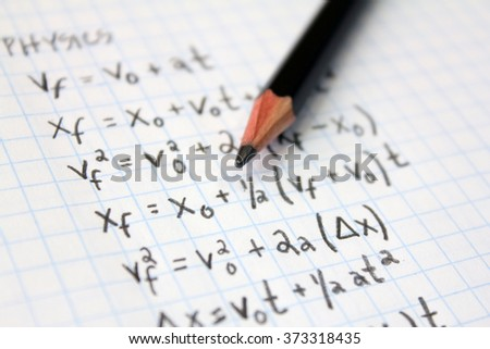 Physics formula on graph paper with pencil - stock photo