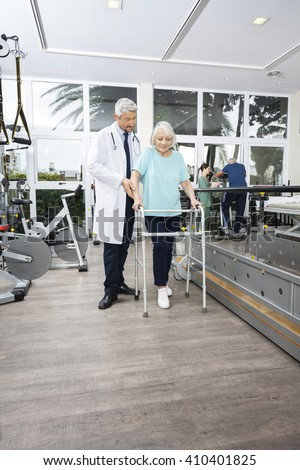Physiotherapist Assisting Woman With Walker In Rehab Center - stock photo