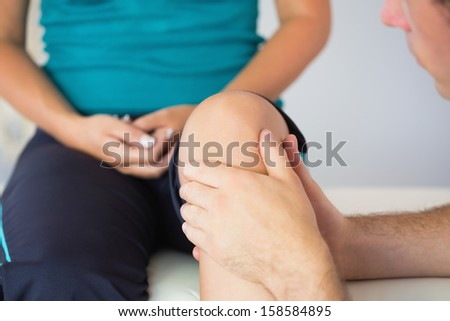 Physiotherapist checking patients knee in bright office