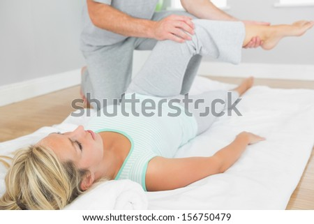 Physiotherapist checking patients leg on a mat on the floor in bright room - stock photo