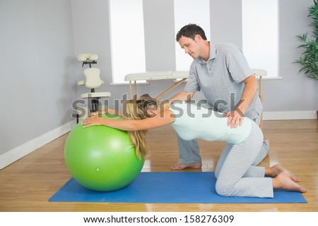 Physiotherapist controlling patient doing exercise with exercise ball in bright room - stock photo