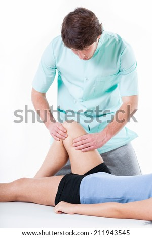Physiotherapist diagnosing patient with painful knee - stock photo