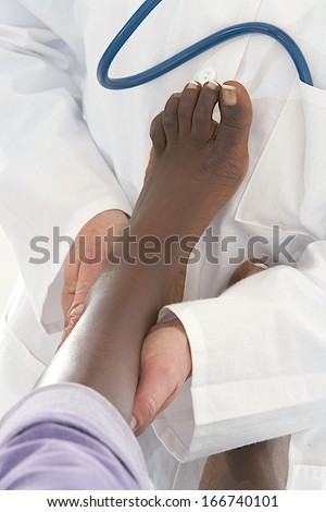 physiotherapist doctor  treating foot tibia of an African American patient  - stock photo