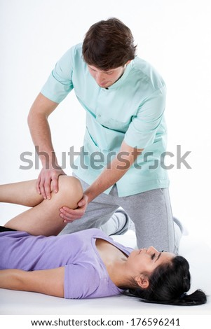 Physiotherapist doing a knee rehabilitation to patient at medical center - stock photo