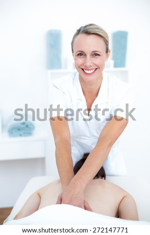 Physiotherapist doing back massage in medical office - stock photo
