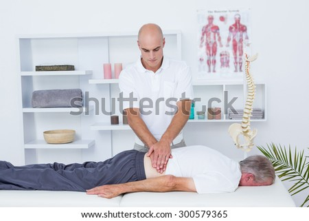 Physiotherapist doing back massage to his patient in medical office - stock photo