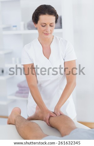 Physiotherapist doing calf massage to her patient in medical office - stock photo