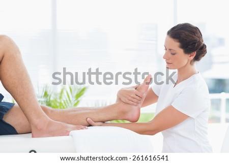 Physiotherapist doing leg massage in medical office - stock photo