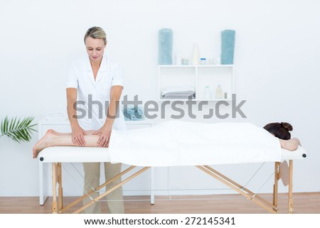 Physiotherapist doing leg massage in medical office - stock photo