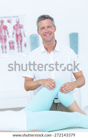 Physiotherapist doing leg massage to his patient in medical office - stock photo