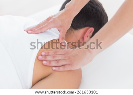 Physiotherapist doing shoulder massage in medical office - stock photo