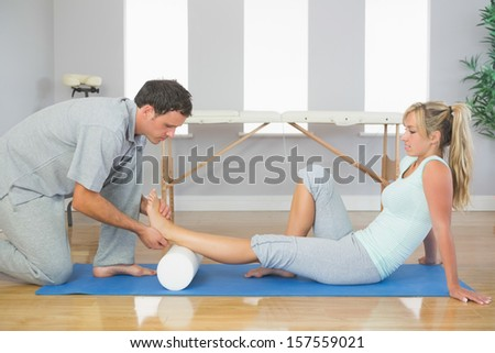 Physiotherapist examining patients foot while sitting on floor in bright room - stock photo