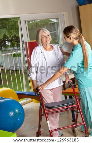 Physiotherapist explaining the use of a walker to a senior woman - stock photo