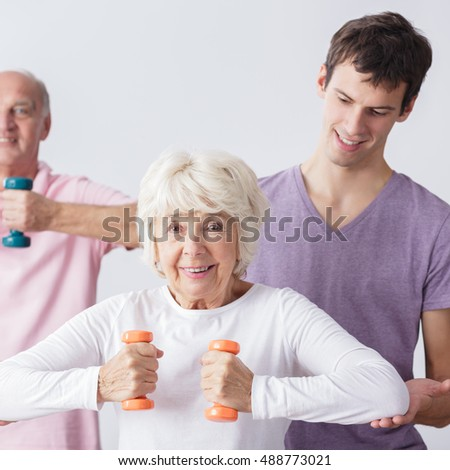 Physiotherapist helping active seniors in exercises
