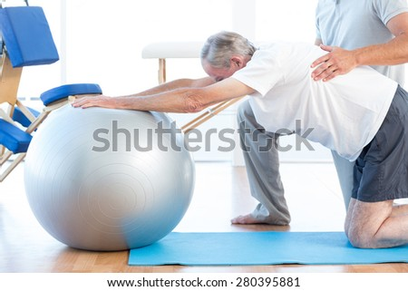 Physiotherapist helping man with exercise ball in medical office - stock photo