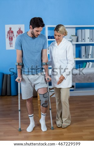 Physiotherapist helping patient to walk with crutches in clinic