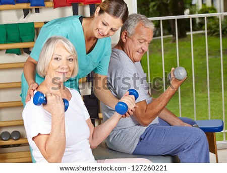 Physiotherapist helping senior people with dumbbell exercises - stock photo