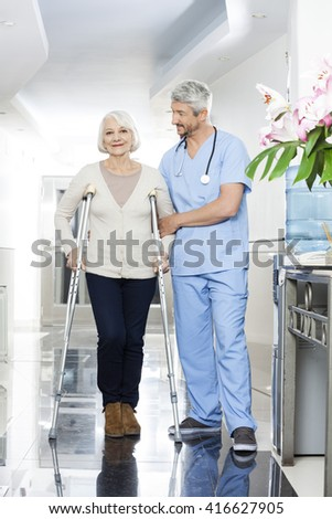 Physiotherapist Helping Senior Woman With Crutches - stock photo