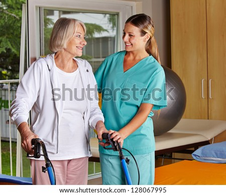 Physiotherapist helping senior woman with walker at remedial gymnastics