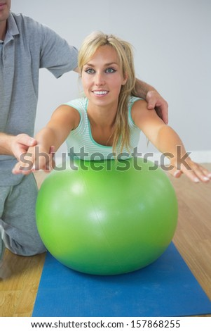 Physiotherapist holding patient doing exercise on exercise ball in bright room - stock photo
