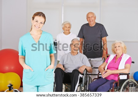 Physiotherapist in front of group of senior people in a nursing home - stock photo
