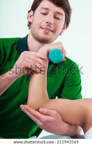 Physiotherapist insuring patient during exercise with dumbbell - stock photo