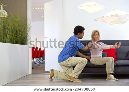 Physiotherapist makes a house call to consult with a middle aged woman, suffering from lower back pains, at her place of work - stock photo