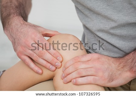 Physiotherapist massaging a painful knee in a room - stock photo
