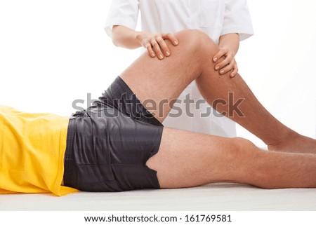 Physiotherapist massaging and examining injured leg - stock photo