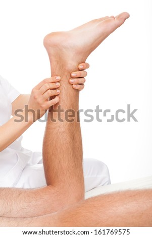 Physiotherapist  massaging man's calf on white isolated background - stock photo