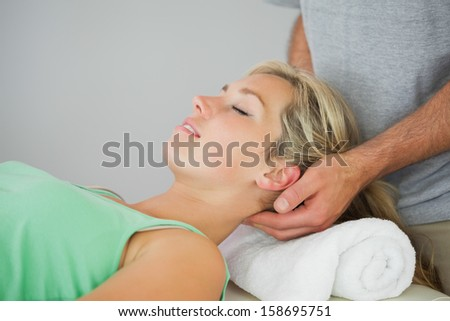 Physiotherapist massaging patients head in bright office - stock photo