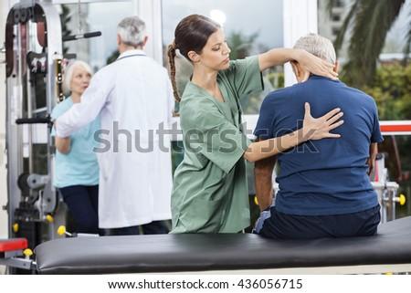Physiotherapist Massaging Senior Man's Back - stock photo