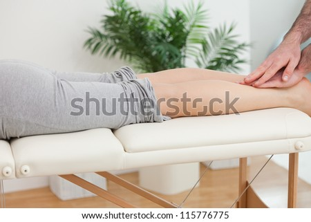 Physiotherapist massaging the legs of a woman in a physio room - stock photo