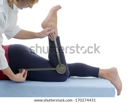Physiotherapist measuring active range of motion of older patient's lower limb using manual goniometer - stock photo
