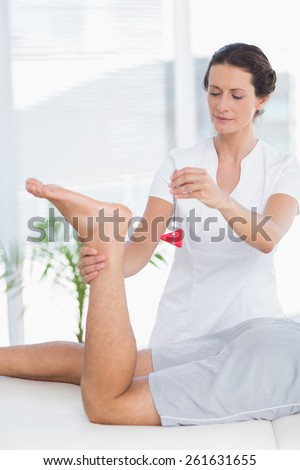 Physiotherapist using reflex hammer in medical office - stock photo