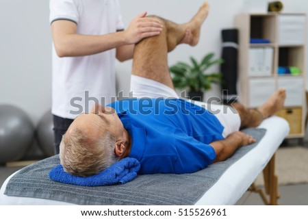 Physiotherapist working with an elderly patient doing mobility and functionality exercises with his left knee as he lies in an examination couch