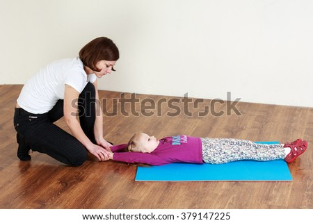Physiotherapy for children. Trainer is doing stretching with a little girl lying on a mat  - stock photo