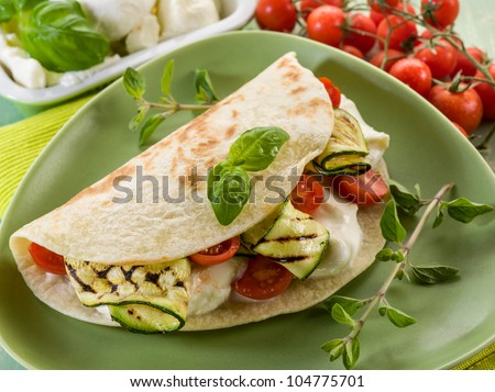 piadina with mozzarella, grelled zucchinis and tomatoes,  typical italian sandwich - stock photo