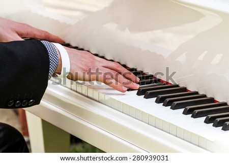 Pianist playing the white piano - stock photo