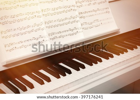 Piano keyboard and musical notes close up - stock photo