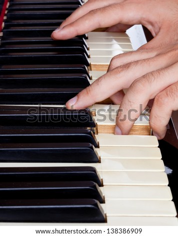 Piano keyboard made of ivory with hands. - stock photo