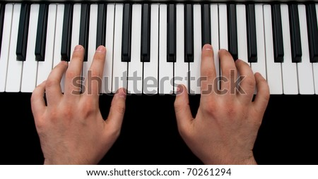 piano keyboard with hands on black background - stock photo