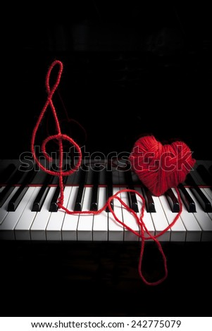 Piano keyboard with treble clef and heart made with wool - stock photo