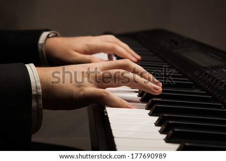 Piano keys and human hands close-up